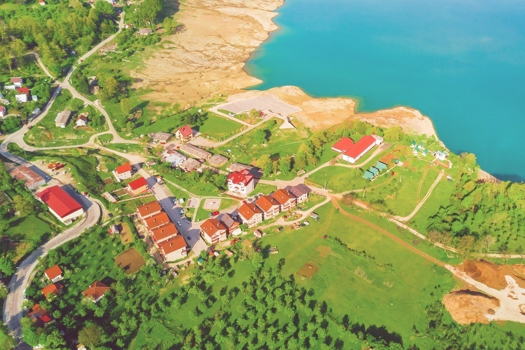 Top view of the small resort town with gardens on the shore of the lake